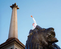 An England football fan celebrates atop one Trafalgar Square's famous lion statues in London. October 2001