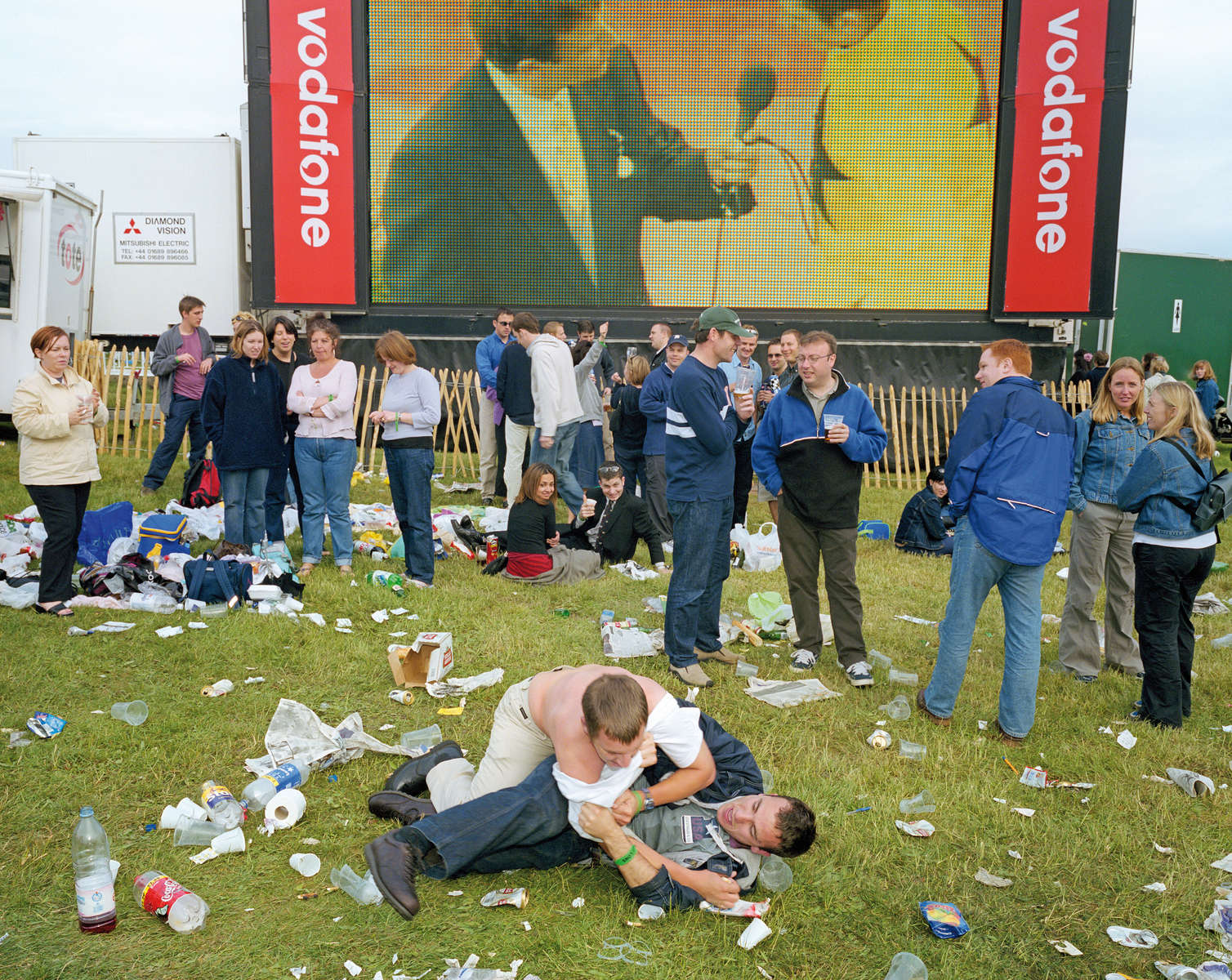 Two young men fool about on the grass beneath a screen showing the action on Derby Day at Epsom Downs Racecourse. June 2001