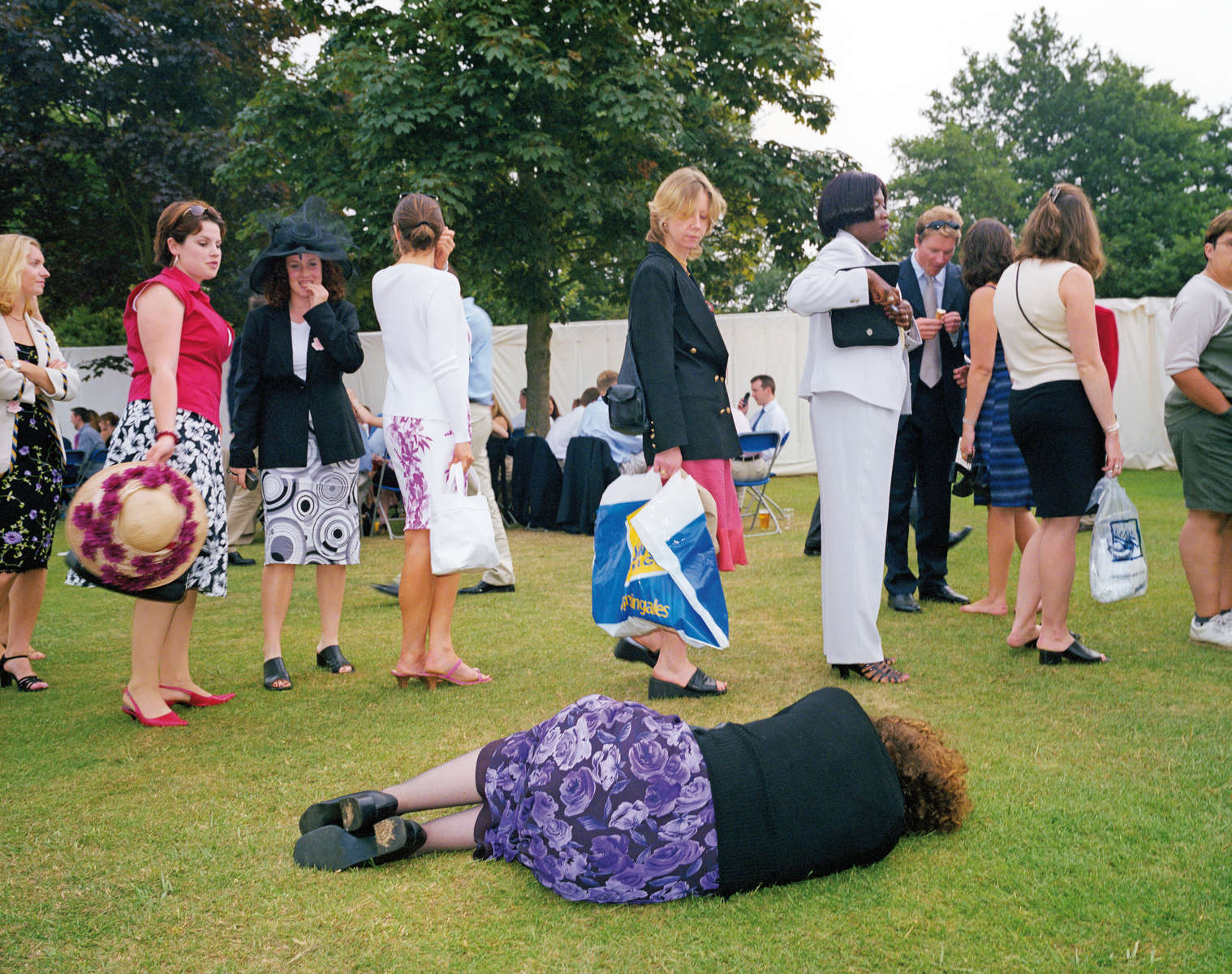 A woman lies on the grass next to the queue for the ladies' toilet at the Henley Royal Regatta. July 2001