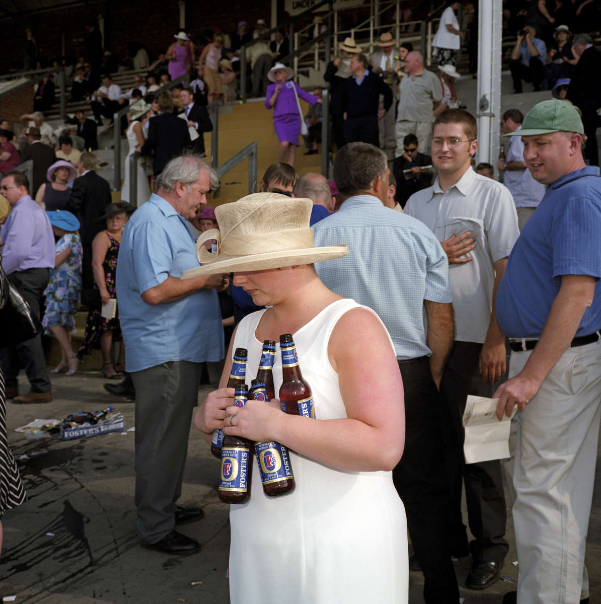 A woman clutches five bottles of lager on Ladies Day at Royal Ascot. June 2001