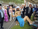 A female visitor to Royal Ascot hangs from the support of a hospitality tent. June 2002