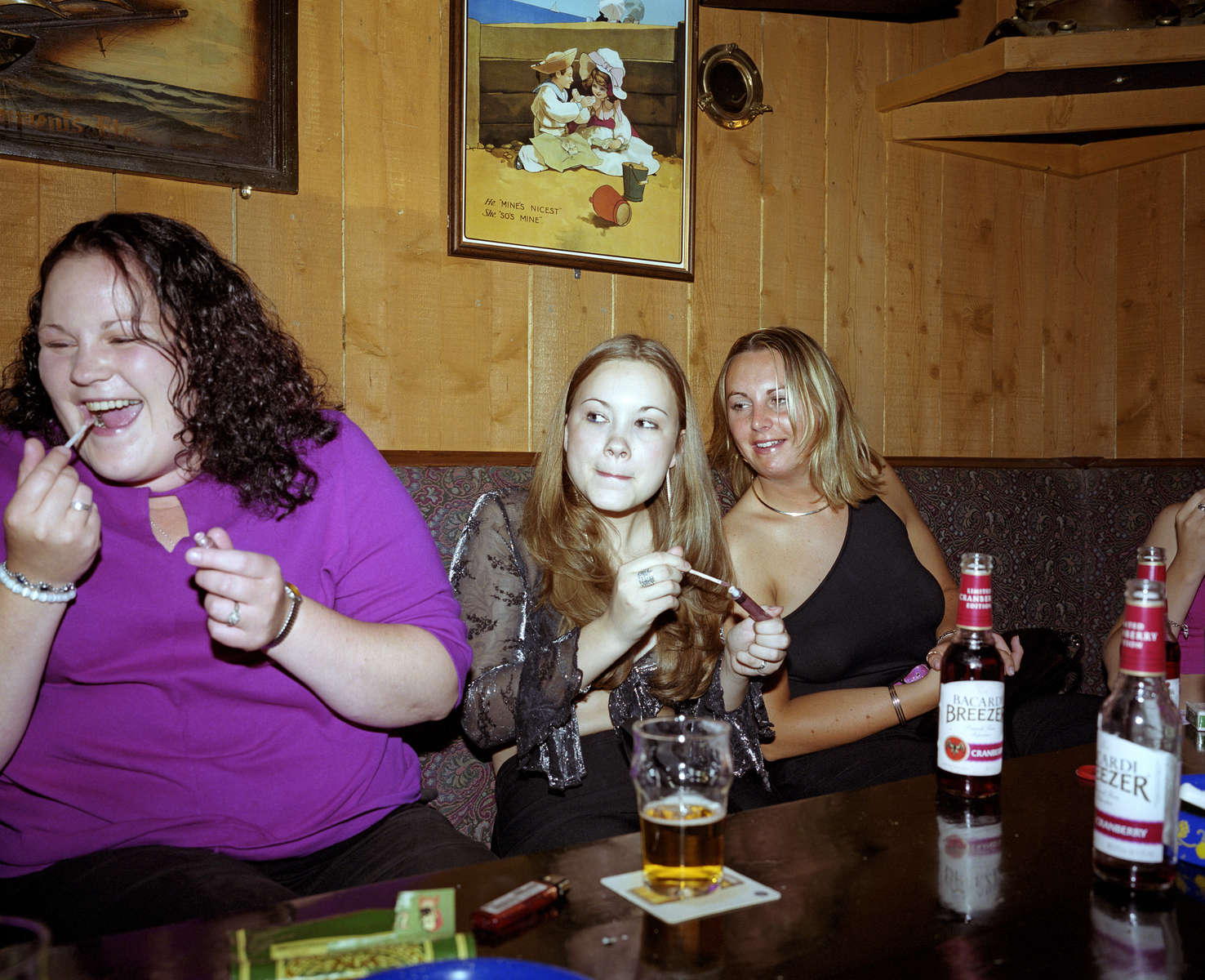 Young women put on lipgloss in a pub at the beginning of a night out in Newquay. July 2001