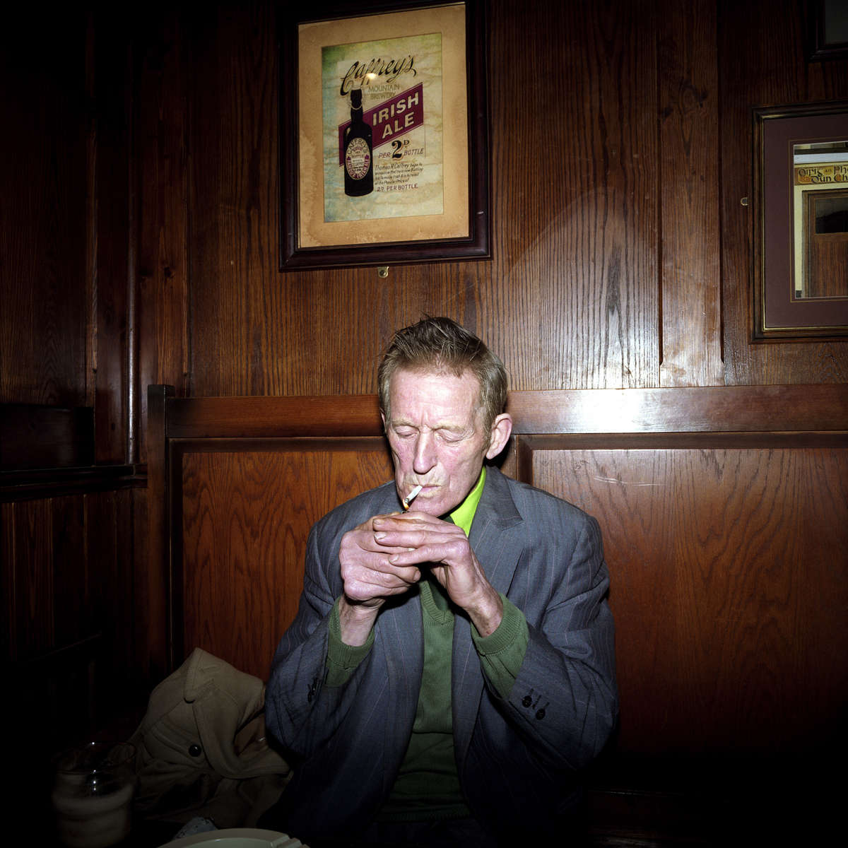 In a north London pub an elderly man lights up a cigarette to accompany his first alcoholic drink since undergoing surgery 12 months earlier. March 2001