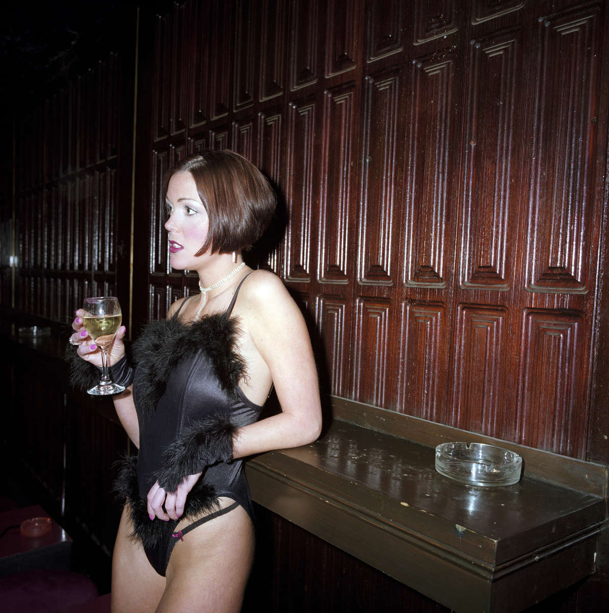 An exotic dancer with a glass of white wine at SophistiCats Gentlemen's Club in central London. March 2001