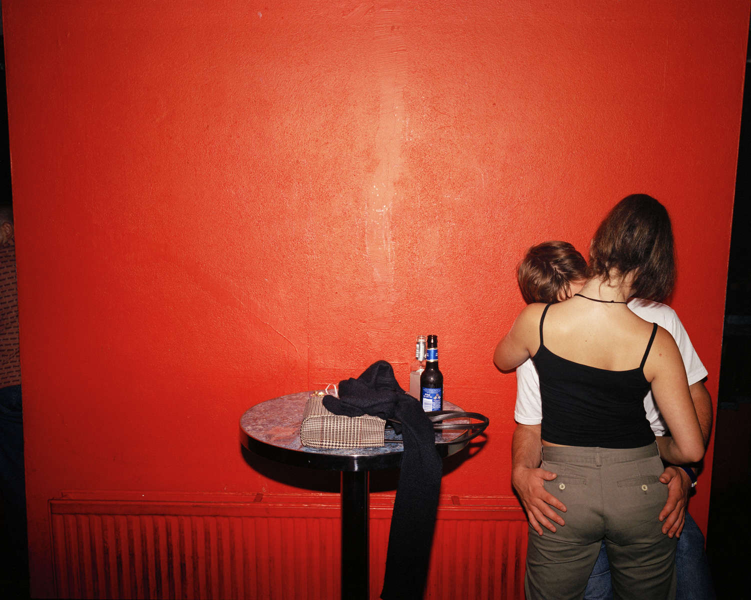 A young couple kiss passionately by a red wall in a Newquay nightclub. July 2001
