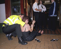 A woman in distress, seated on the pavement outside a bar during a night out in Basingstoke town centre, is attended to by a police officer. September 2004