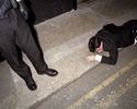 A police officer stands over a man found lying in the gutter near Union Street in Plymouth. November 2001