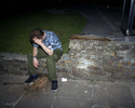 A young man sat on a wall feels the effects of a night out in Newquay, Cornwall. July 2001