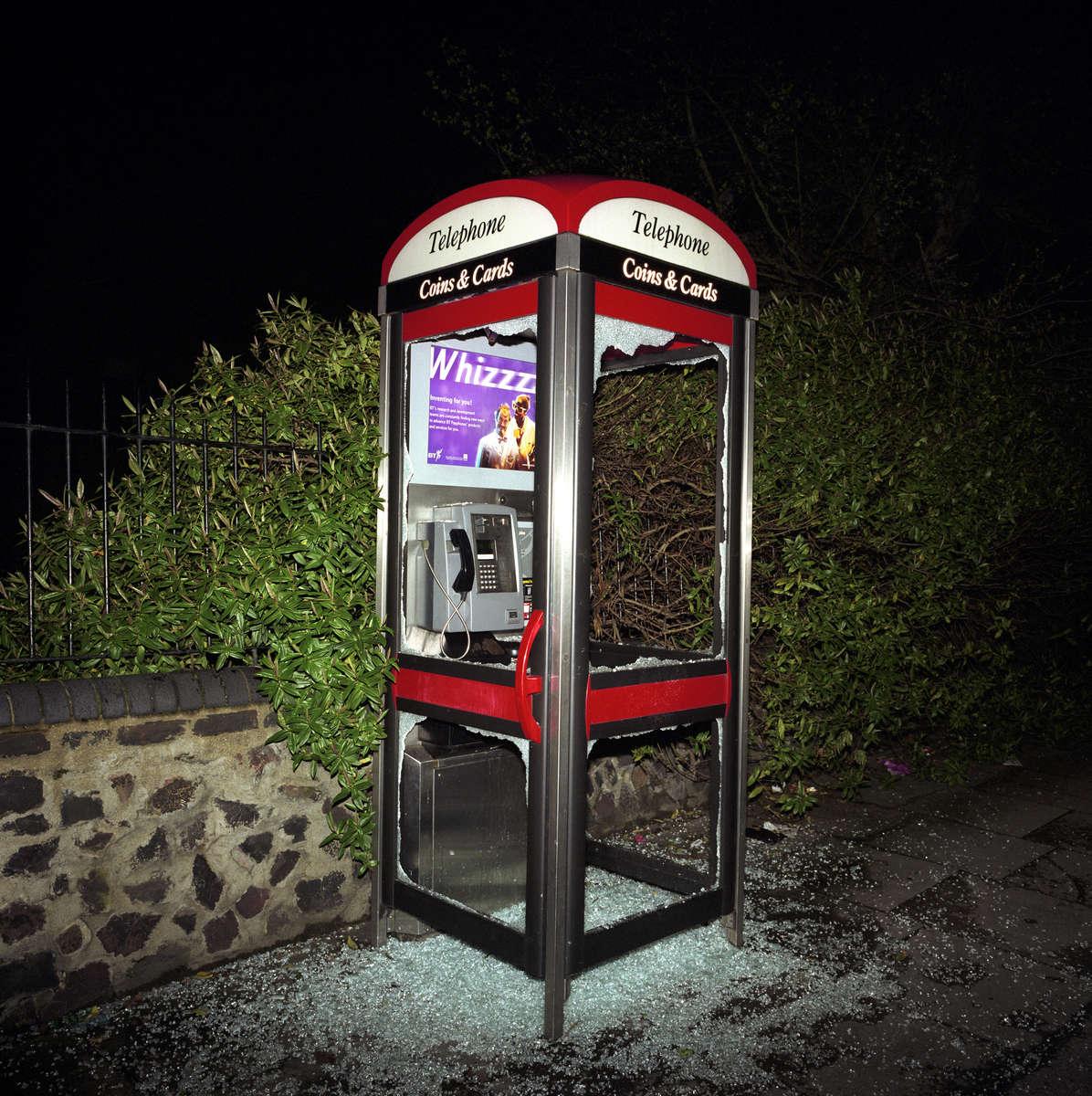 A vandalised telephone box in north London. April 2001
