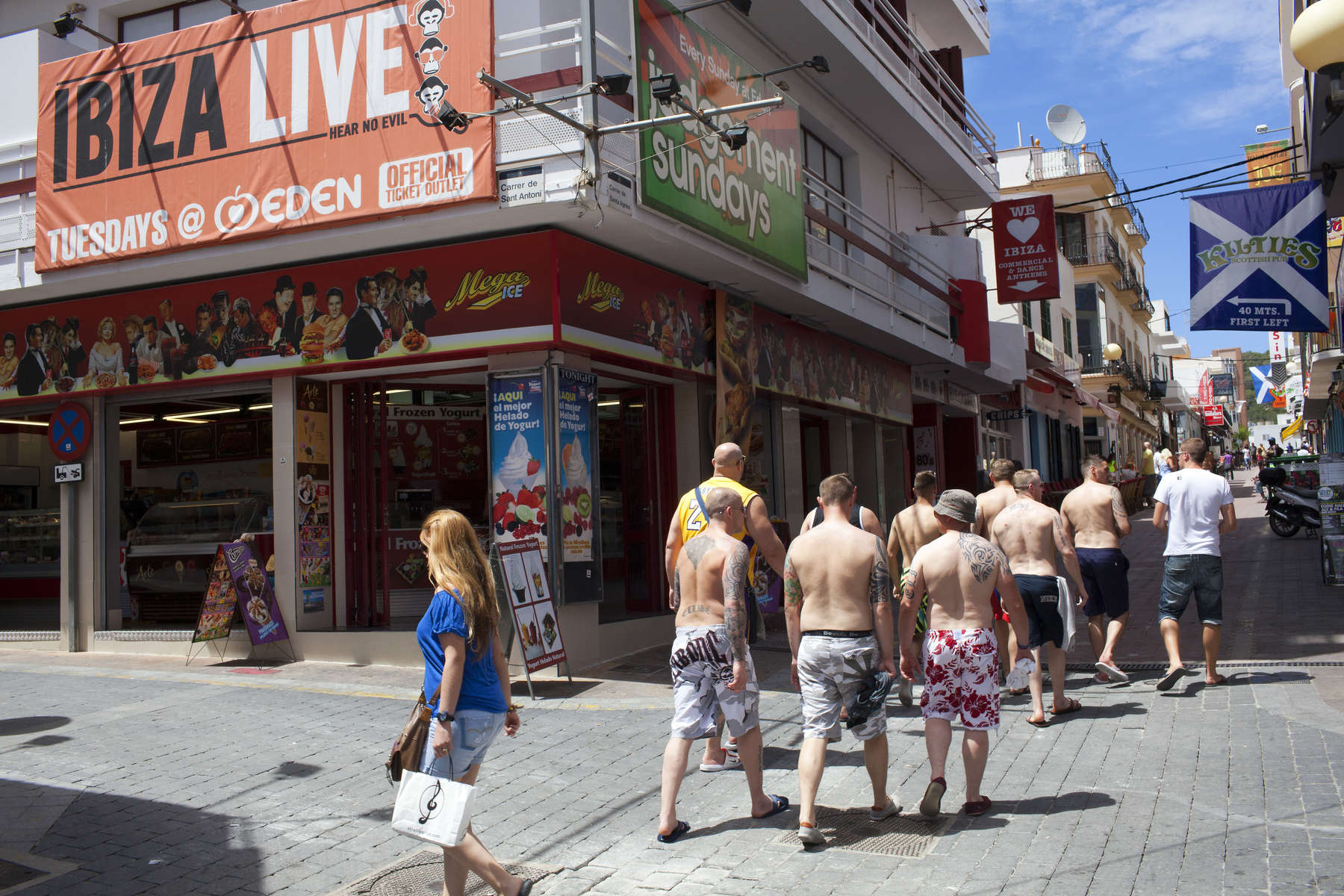 15:14 A group of British men, most of who are not wearing shirts, head in to the part of San Antonio town, Ibiza, known as the West End. The fine for not wearing a top in town centres and public areas is up to €750.