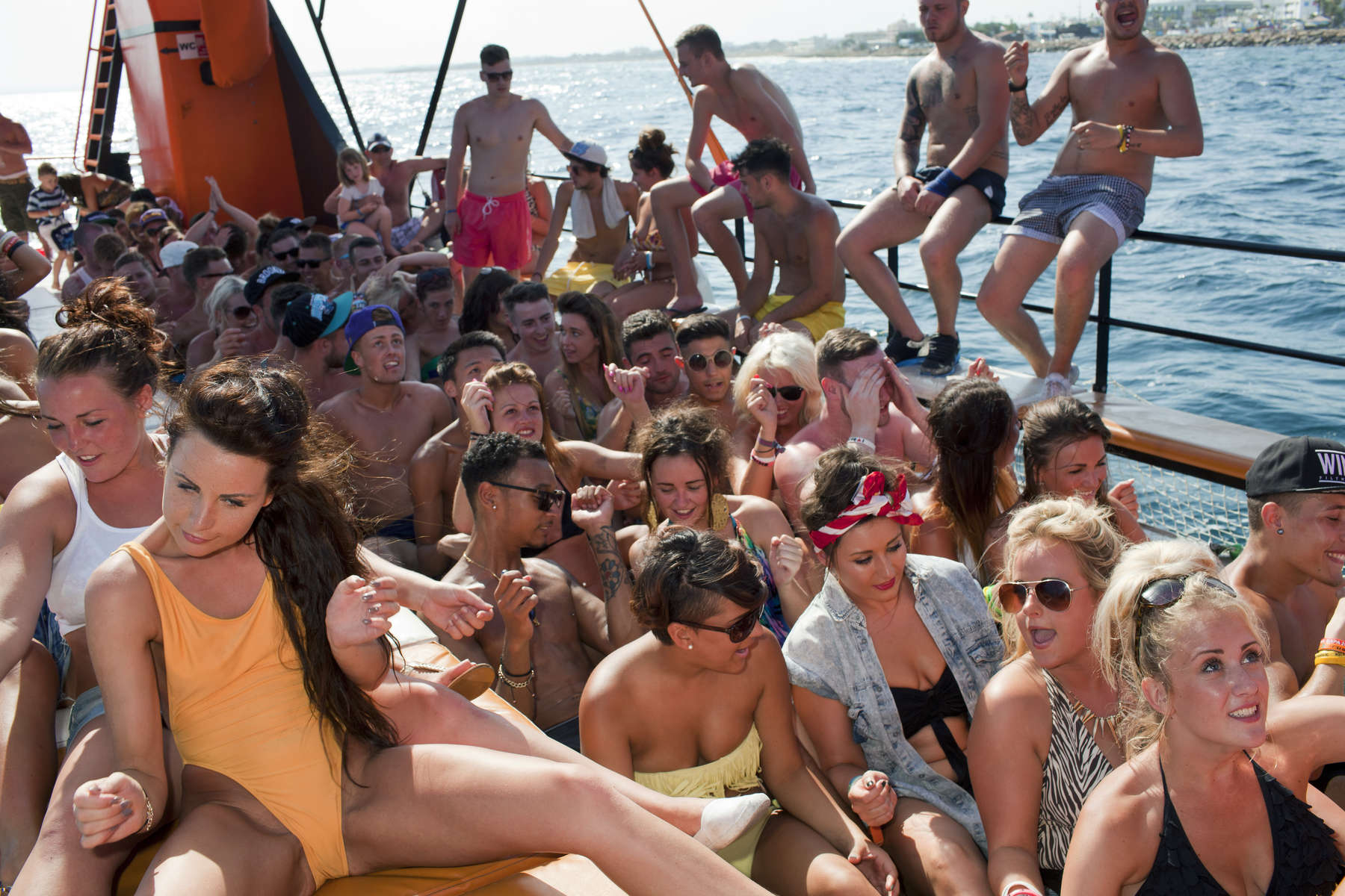16:25 An afternoon boat party for the many British seasonal bar workers and promoters in Ayia Napa, Cyprus. They are performing a dance to the 1979 funk anthem recorded by The Gap Band, Oops Up Side Your Head.