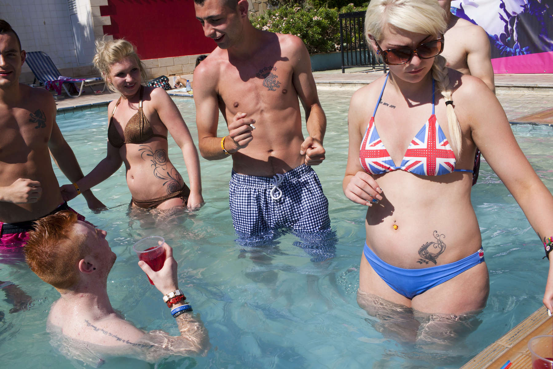 15:47 A group of friends from Scotland, smoke, drink and chat in the sunshine at an afternoon pool party, hosted at Club Aqua in Ayia Napa, Cyprus.