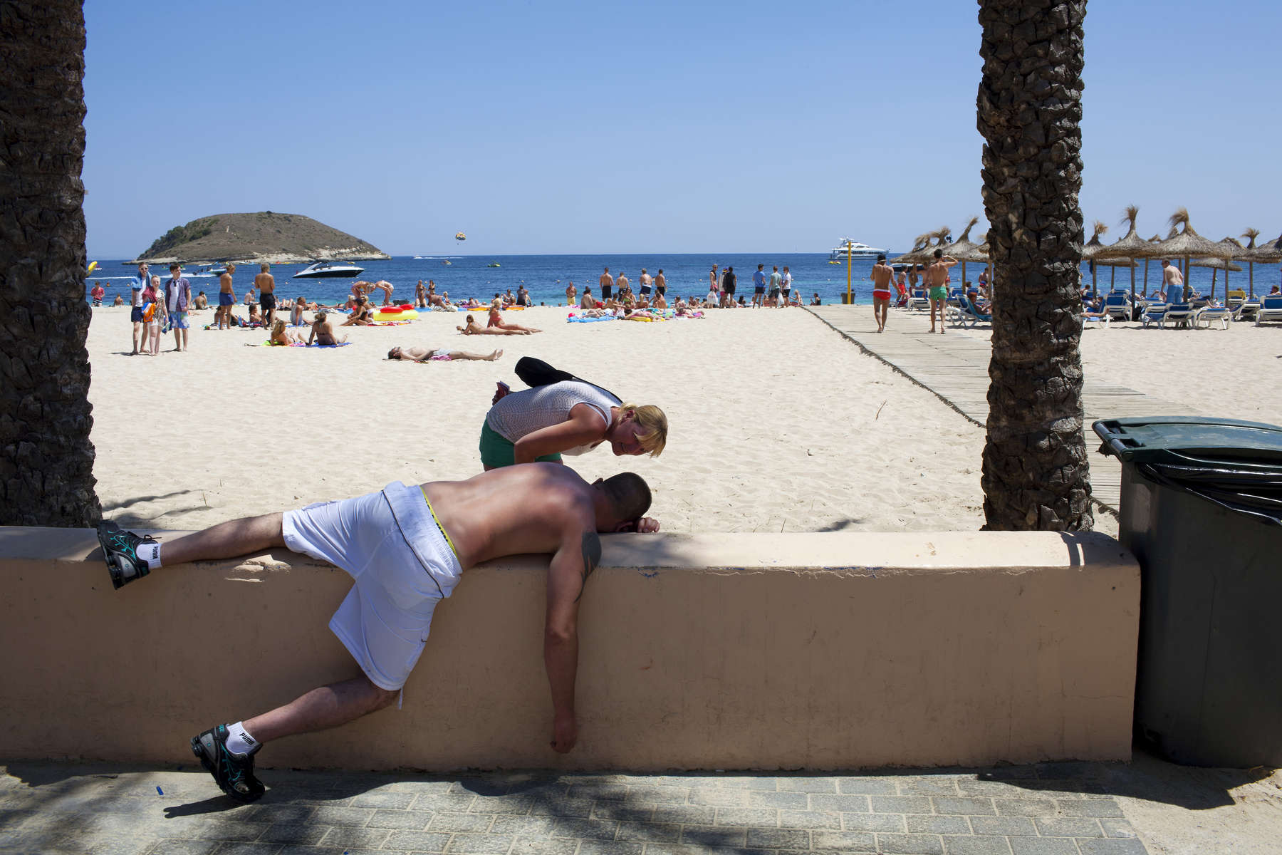 15:08 A Scottish woman checks on the well being of a British man slumped on a wall next to Magaluf beach, Majorca.