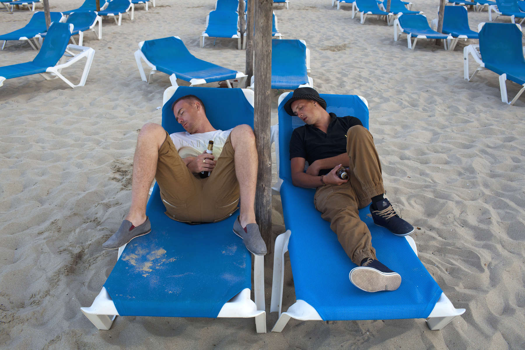 06.58 two British men hold their bottles of San Miguel beer as they sleep of the nights excesses on sun beds at the beach at Magaluf, Majorca.