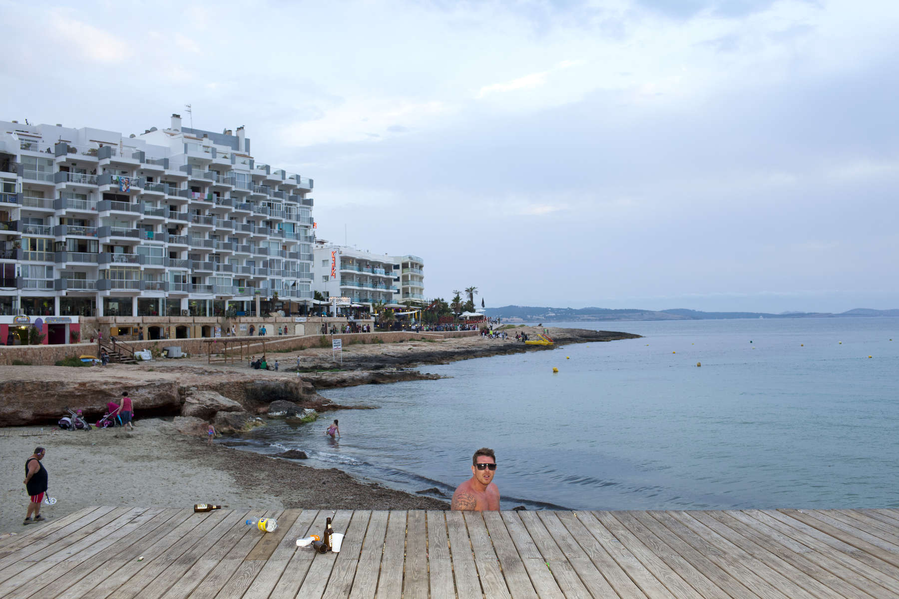 20:58 A man from the British Midlands relieves himself by a beach in San Antonio, Ibiza, as children play behind him. The fine for urinating in the street and public spaces is up to €1,500.