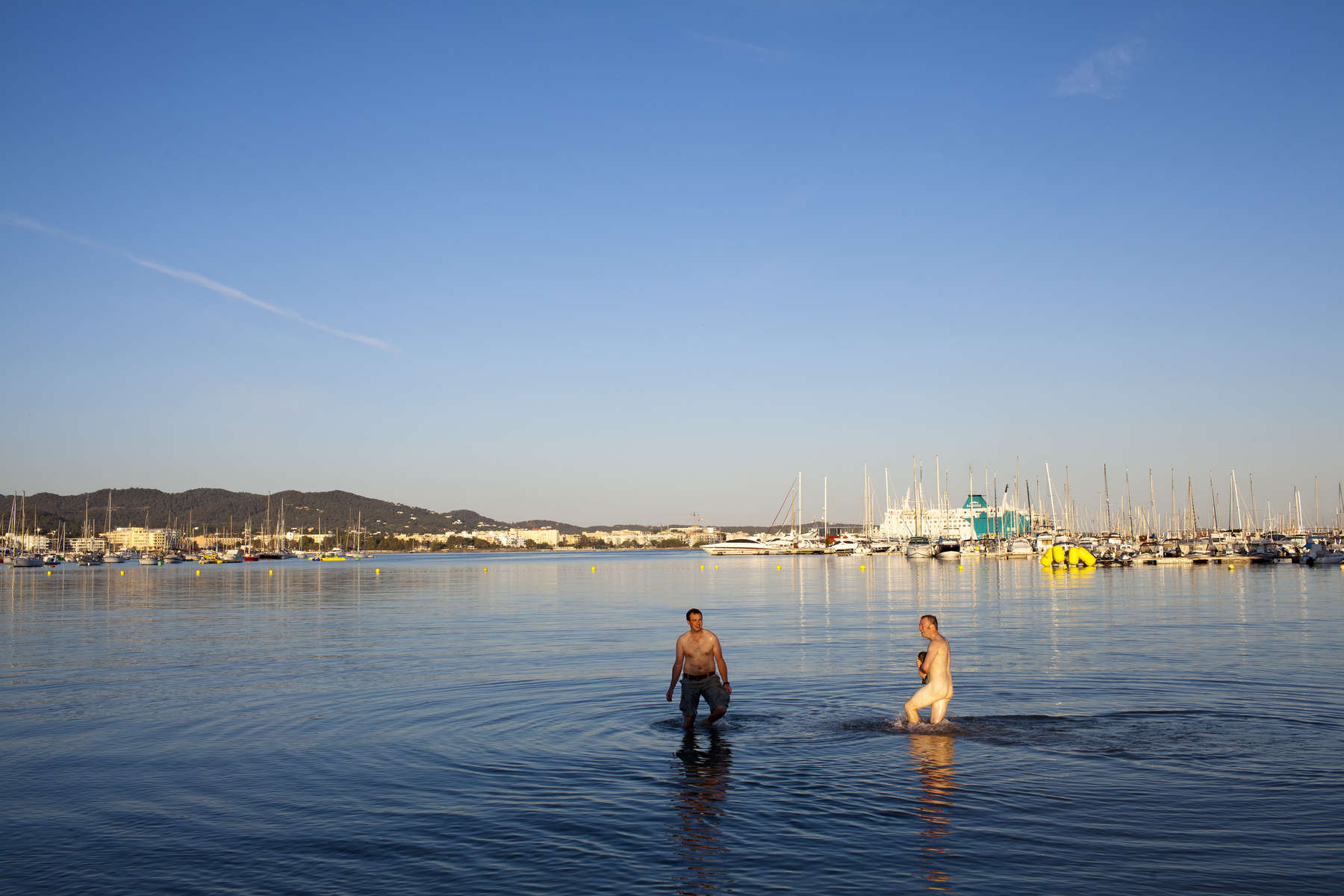 07:16 A naked man holding his clothes in the sea at San Antonio beach, Ibiza. He arrived with friends late the previous evening on a Monarch Airlines flight from Manchester.