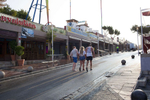 08:05 Three British friends make their way back to their accommodation as the sun rises over the main bar strip in Magaluf, Ibiza.