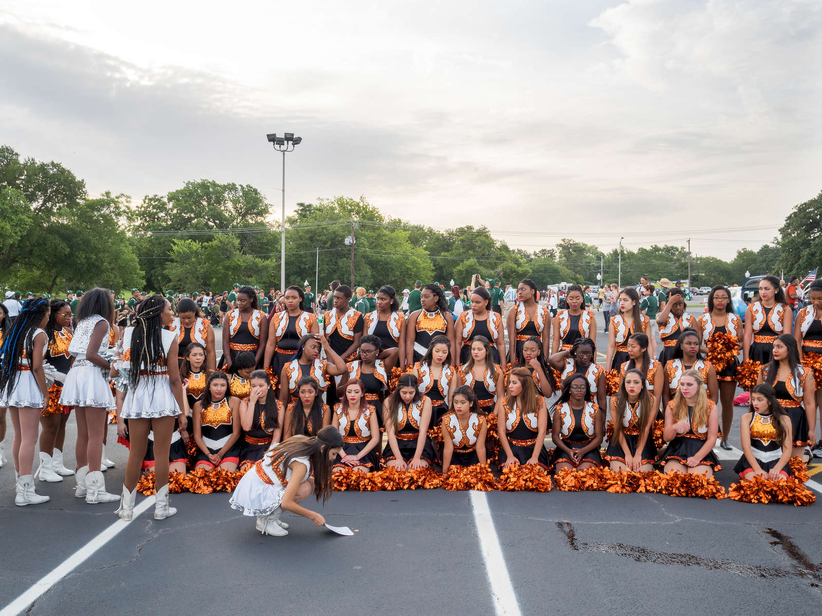 Cheerleaders prepare for a group photograph ahead of the 4th July Independence Day parade in Arlington.Dallas is a major city in Texas and is the largest urban center of the fourth most populous metropolitan area in the United States. The city ranks ninth in the U.S. and third in Texas after Houston and San Antonio. The city's prominence arose from its historical importance as a center for the oil and cotton industries, and its position along numerous railroad lines.For two weeks in the summer of 2015, photographer Peter Dench visited Dallas to document the metroplex in his epic reportage, DENCH DOES DALLAS.Photographed using an Olympus E-M5 Mark II©Peter Dench/Getty Images Reportage