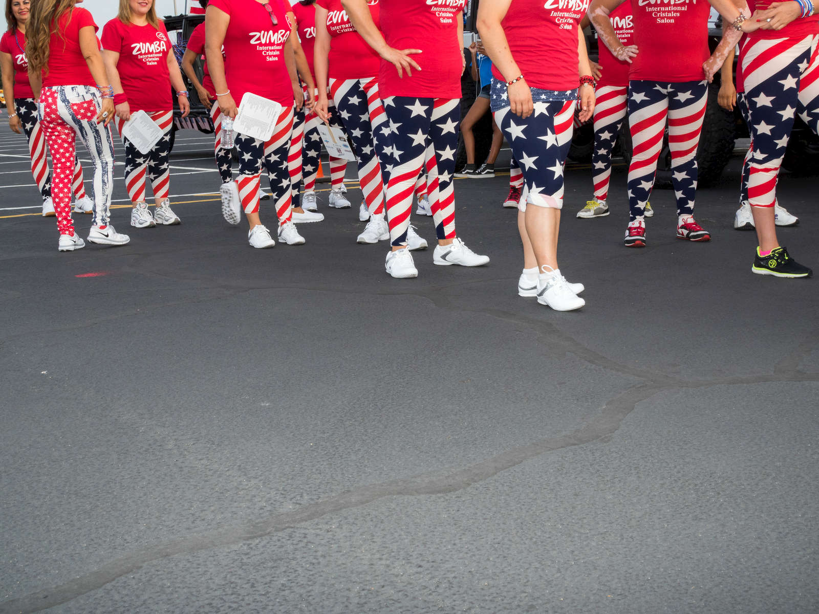 Zumba dancers prepare for the 4thy July parade in Alrington, a city 20 miles west of downtown Dallas.Dallas is a major city in Texas and is the largest urban center of the fourth most populous metropolitan area in the United States. The city ranks ninth in the U.S. and third in Texas after Houston and San Antonio. The city's prominence arose from its historical importance as a center for the oil and cotton industries, and its position along numerous railroad lines.For two weeks in the summer of 2015, photographer Peter Dench visited Dallas to document the metroplex in his epic reportage, DENCH DOES DALLAS.Photographed using an Olympus E-M5 Mark II©Peter Dench/Getty Images Reportage