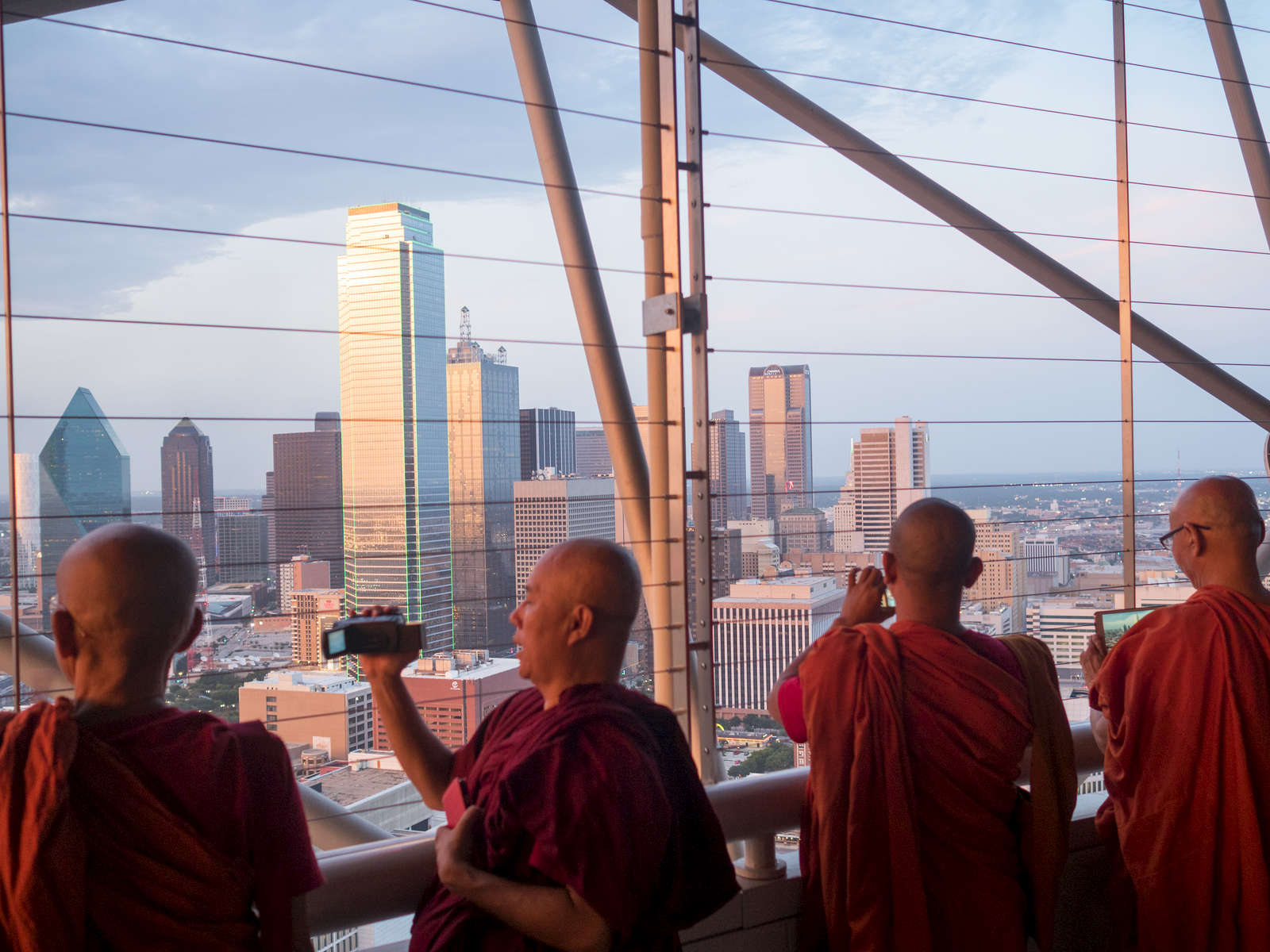 Buddhist Monks take in the view from the top of the Reunion Tower across the Dallas skyline dominated by the bulding of Bank of America.Dallas is a major city in Texas and is the largest urban center of the fourth most populous metropolitan area in the United States. The city ranks ninth in the U.S. and third in Texas after Houston and San Antonio. The city's prominence arose from its historical importance as a center for the oil and cotton industries, and its position along numerous railroad lines.For two weeks in the summer of 2015, photographer Peter Dench visited Dallas to document the metroplex in his epic reportage, DENCH DOES DALLAS.Photographed using an Olympus E-M5 Mark II©Peter Dench/Getty Images Reportage