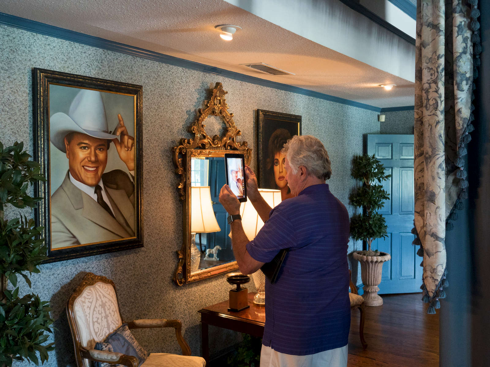 A visitor to the Southfork ranch takes a photograph of a painting of J. R. Ewing, one of the main characters from the TV show, Dallas, that aired from April 2, 1978, to May 3, 1991, on CBS. The series revolves around a wealthy and feuding Texan family, the Ewings, who own the independent oil company Ewing Oil and the cattle-ranching land of Southfork.Dallas is a major city in Texas and is the largest urban center of the fourth most populous metropolitan area in the United States. The city ranks ninth in the U.S. and third in Texas after Houston and San Antonio. The city's prominence arose from its historical importance as a center for the oil and cotton industries, and its position along numerous railroad lines.For two weeks in the summer of 2015, photographer Peter Dench visited Dallas to document the metroplex in his epic reportage, DENCH DOES DALLAS.Photographed using an Olympus E-M5 Mark II©Peter Dench/Getty Images Reportage