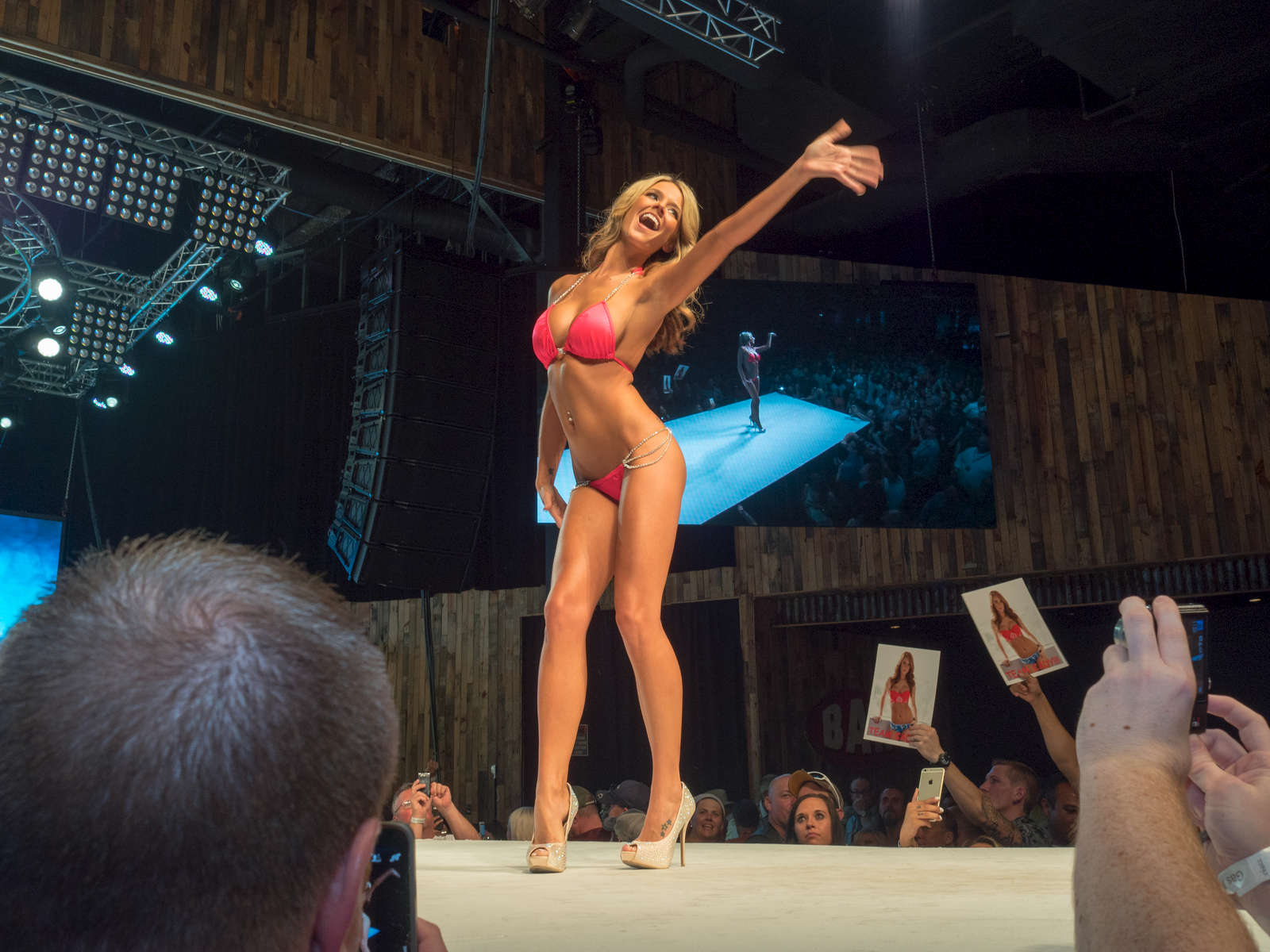 A finalist on stage at the Twin Peaks 2015 National Bikini Contest where around 68 girls from the USA competed for the crown for Miss Twin Peaks 2015, hosted at Gas Monkey Live, Dallas on the 24th June.Twin Peaks is a chain of sports bars and restaurants (colloquially referred to as breastaurants) based in Dallas, Texas. The chain is known for having its waitresses dress in revealing uniforms that consist of cleavage- and midriff-revealing red plaid (or sometimes black bikini) tops, as well as khaki short shorts. At other times, waitresses wear revealing seasonal or themed outfits. Restaurants are decorated in the theme of a wilderness lodge and serve a mix of American, Southwest and Southern cuisines as well as alcohol. The chain's slogan is {quote}Eats. Drinks. Scenic Views.{quote}Dallas is a major city in Texas and is the largest urban center of the fourth most populous metropolitan area in the United States. The city ranks ninth in the U.S. and third in Texas after Houston and San Antonio. The city's prominence arose from its historical importance as a center for the oil and cotton industries, and its position along numerous railroad lines.For two weeks in the summer of 2015, photographer Peter Dench visited Dallas to document the metroplex in his epic reportage, DENCH DOES DALLAS.Photographed using an Olympus E-M5 Mark II©Peter Dench/Getty Images Reportage