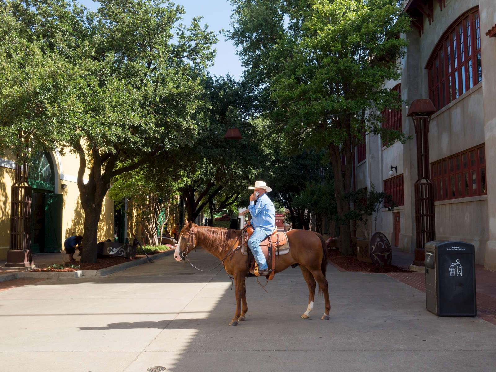 A man in a cowboy hat talks on his cell phone while sat on a horse.Dallas is a major city in Texas and is the largest urban center of the fourth most populous metropolitan area in the United States. The city ranks ninth in the U.S. and third in Texas after Houston and San Antonio. The city's prominence arose from its historical importance as a center for the oil and cotton industries, and its position along numerous railroad lines.For two weeks in the summer of 2015, photographer Peter Dench visited Dallas to document the metroplex in his epic reportage, DENCH DOES DALLAS.Photographed using an Olympus E-M5 Mark II©Peter Dench/Getty Images Reportage