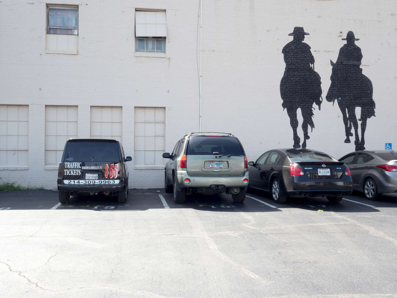 Cowboys painted on to the wall of a car park in south Dallas.Dallas is a major city in Texas and is the largest urban center of the fourth most populous metropolitan area in the United States. The city ranks ninth in the U.S. and third in Texas after Houston and San Antonio. The city's prominence arose from its historical importance as a center for the oil and cotton industries, and its position along numerous railroad lines.For two weeks in the summer of 2015, photographer Peter Dench visited Dallas to document the metroplex in his epic reportage, DENCH DOES DALLAS.Photographed using an Olympus E-M5 Mark II©Peter Dench/Getty Images Reportage