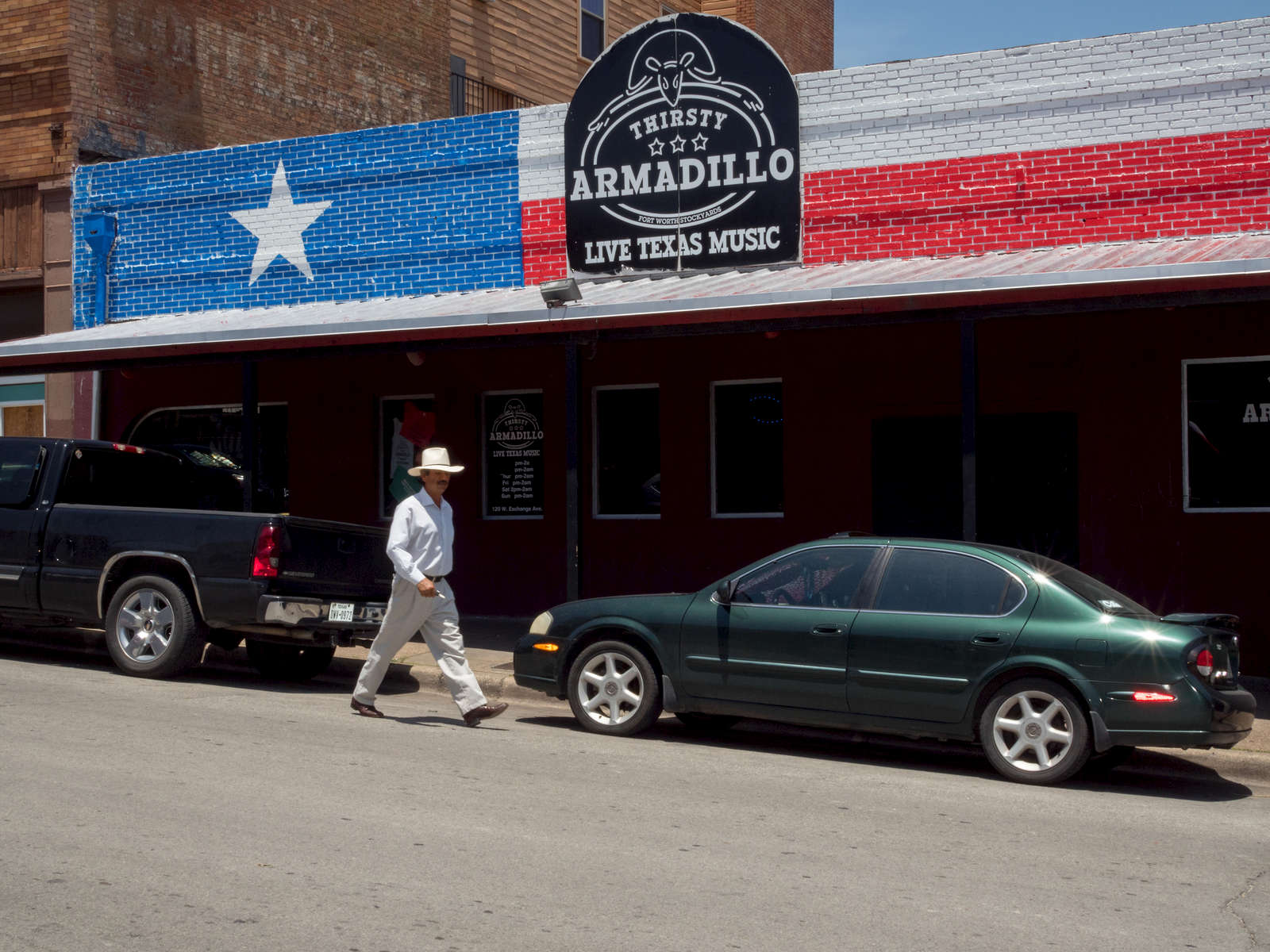 A man walks past the Armadillo bar on West Exchange Avenue, Stockyards, Fort Worth.The Fort Worth Stockyards is a historic district that is located in Fort Worth, Texas, north of the central business district. The 98-acre (40 ha) district was listed on the National Register of Historic Places as Fort Worth Stockyards Historic District in 1976.They are a former livestock market which operated under various owners from 1866.Dallas is a major city in Texas and is the largest urban center of the fourth most populous metropolitan area in the United States. The city ranks ninth in the U.S. and third in Texas after Houston and San Antonio. The city's prominence arose from its historical importance as a center for the oil and cotton industries, and its position along numerous railroad lines.For two weeks in the summer of 2015, photographer Peter Dench visited Dallas to document the metroplex in his epic reportage, DENCH DOES DALLAS.Photographed using an Olympus E-M5 Mark II©Peter Dench/Getty Images Reportage