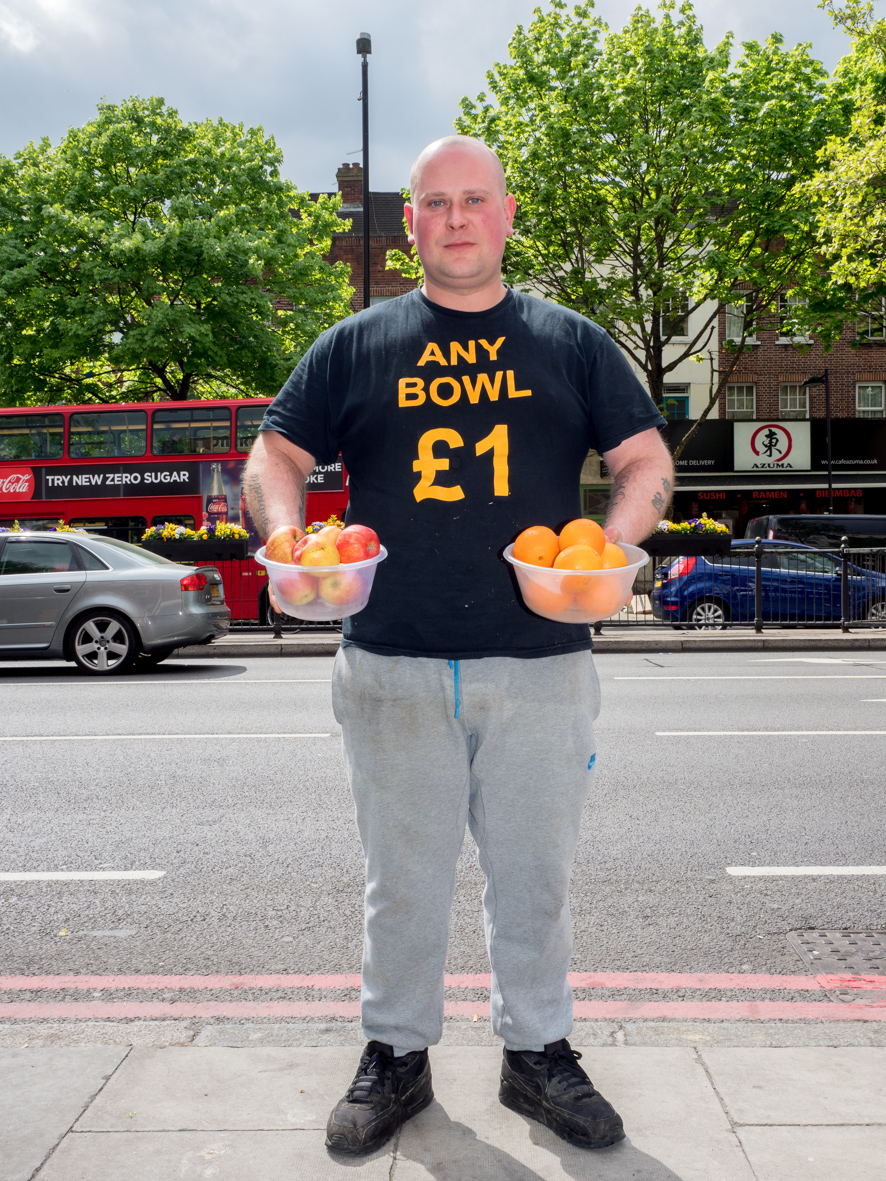 Mark, 32, from Essex selling fruit and vegetables. The business has witnessed price rises in transportation and import costs, according to Mark, as a consequence of Brexit. He is optimistic the business will survive until things settle down and will {quote}Keep going{quote}. Holloway, London.
