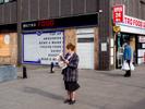 A woman reads The Daily Mirror newspaper. Archway, London.