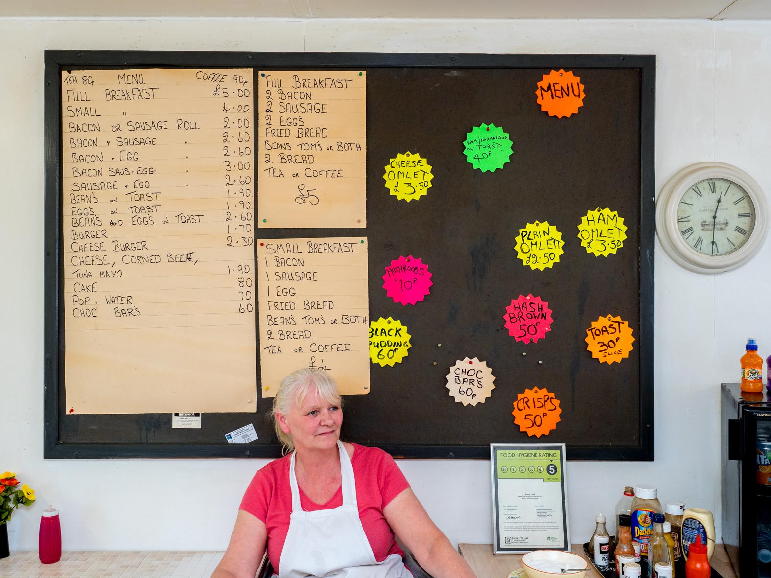 Babs sat under the menu board in BABS cafe. Blyth, Nottinghamshire.