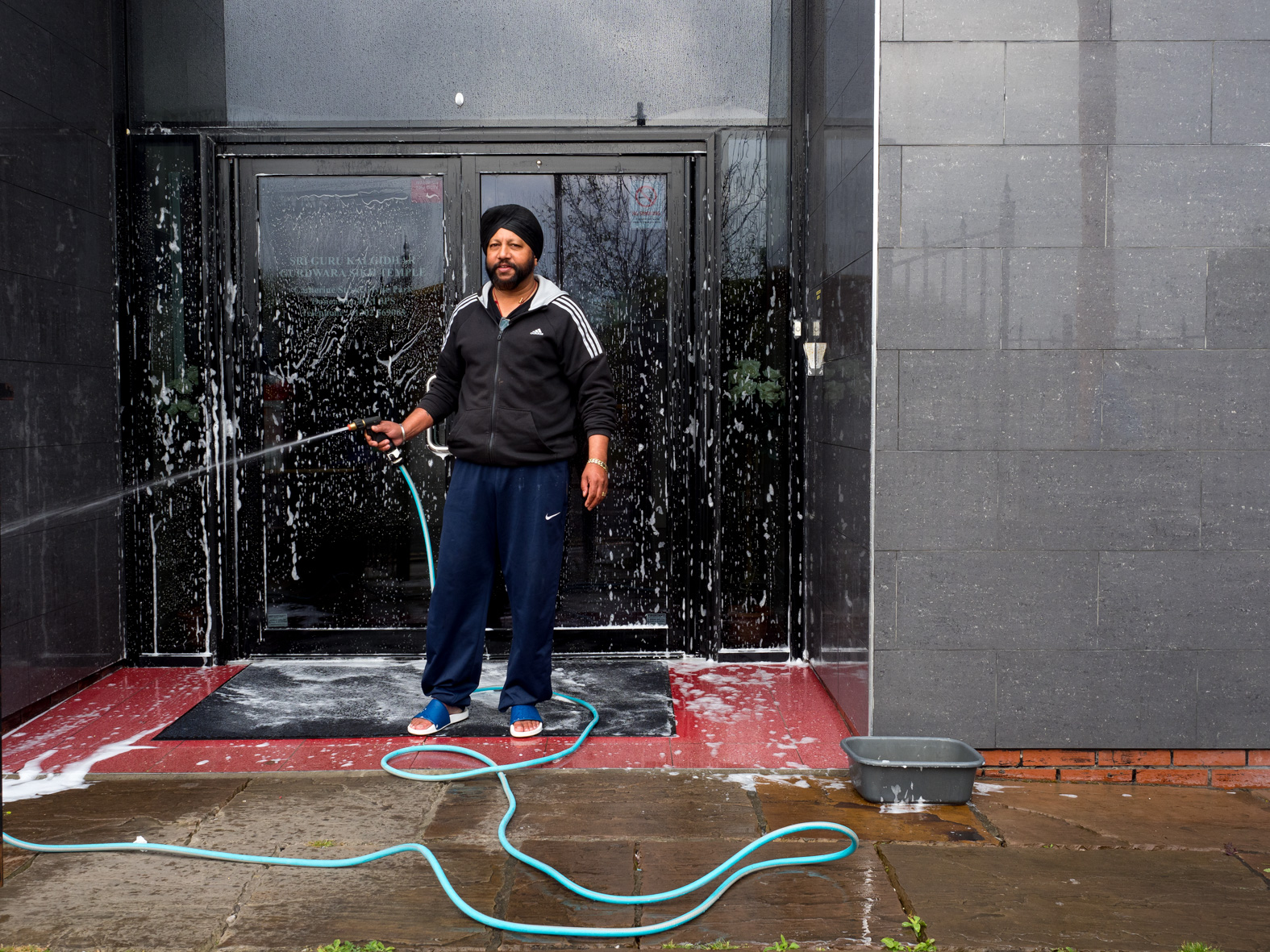 56 year old Sikh, Vaz, hoses down the entrance of Sri Guru Kalgidhar Gurdwara before worshippers arrive on a Sunday. Doncaster, South Yorkshire.
