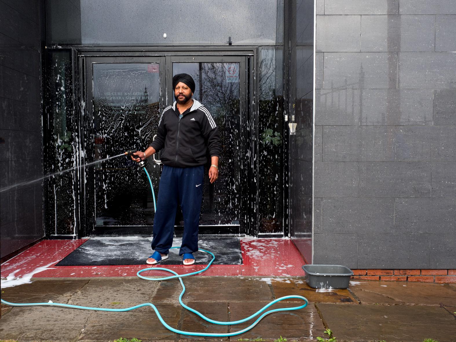 56 year old Sikh, Vaz, hoses down the entrance of Sri Guru Kalgidhar Gurdwara before worshippers arrive on a Sunday. Doncaster, South Yorkshire.