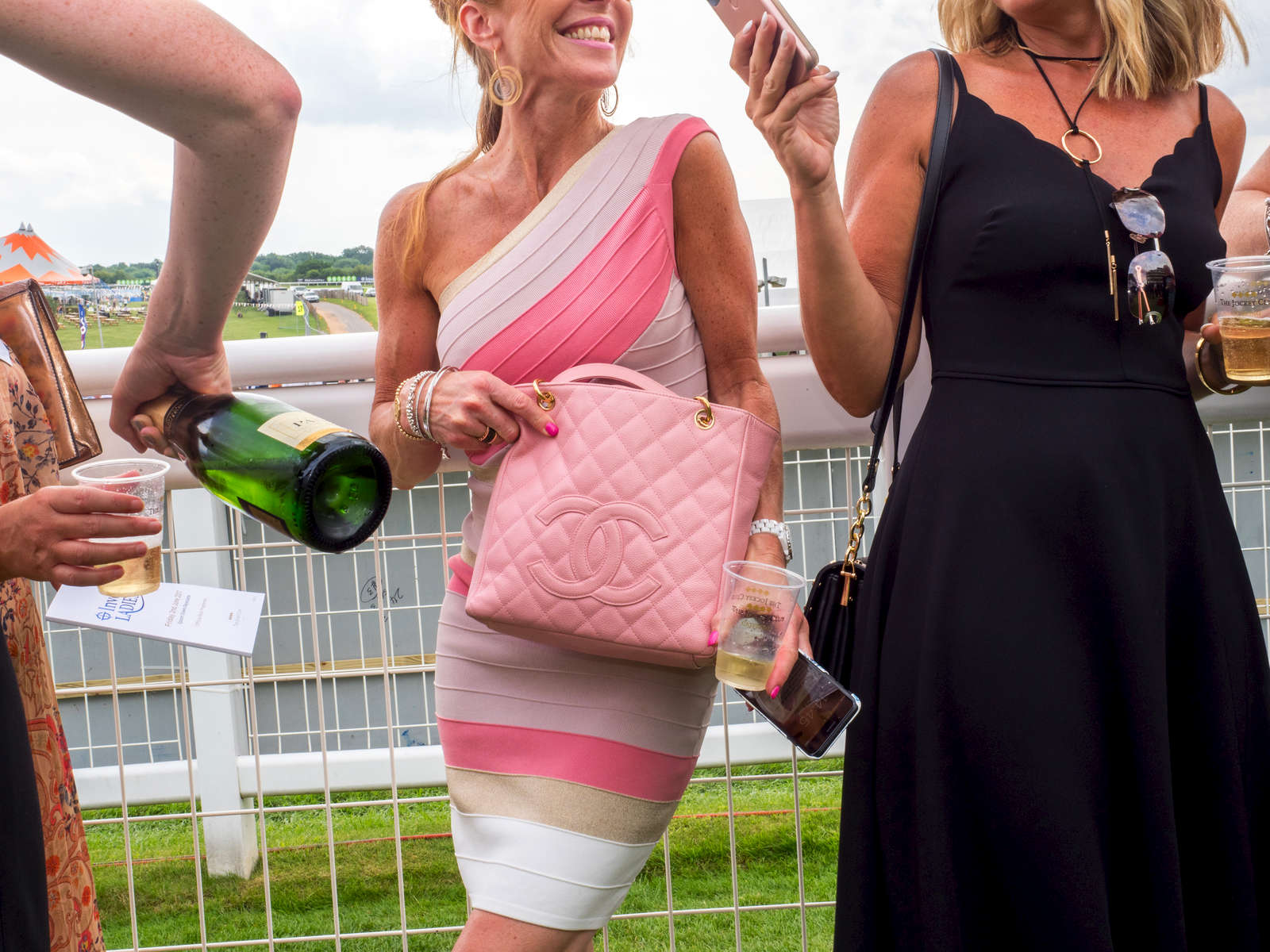 A woman with a Chanel bag socialises with friends at Epsom.Ladies' Day is traditionally held on the first Friday of June, a multitude of ladies and gents head to Epsom Downs Racecourse to experience a day full of high octane racing, music, glamour and fashion.
