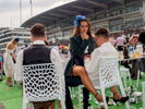 A young woman smokes a cigarette straddled across a man's lap on Ladies' Day at Epsom.Ladies' Day is traditionally held on the first Friday of June, a multitude of ladies and gents head to Epsom Downs Racecourse to experience a day full of high octane racing, music, glamour and fashion.