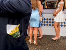 A man utilises his jacket pocket as a holder for his packet of chips.Ladies' Day is traditionally held on the first Friday of June, a multitude of ladies and gents head to Epsom Downs Racecourse to experience a day full of high octane racing, music, glamour and fashion.