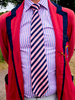 A man wearing the club tie and blazer of Emmanual Cambriddge Boat Club at Henley Royal Regatta, a rowing event held annually on the River Thames by the town of Henley-on-Thames, England. It was established on 26 March 1839.