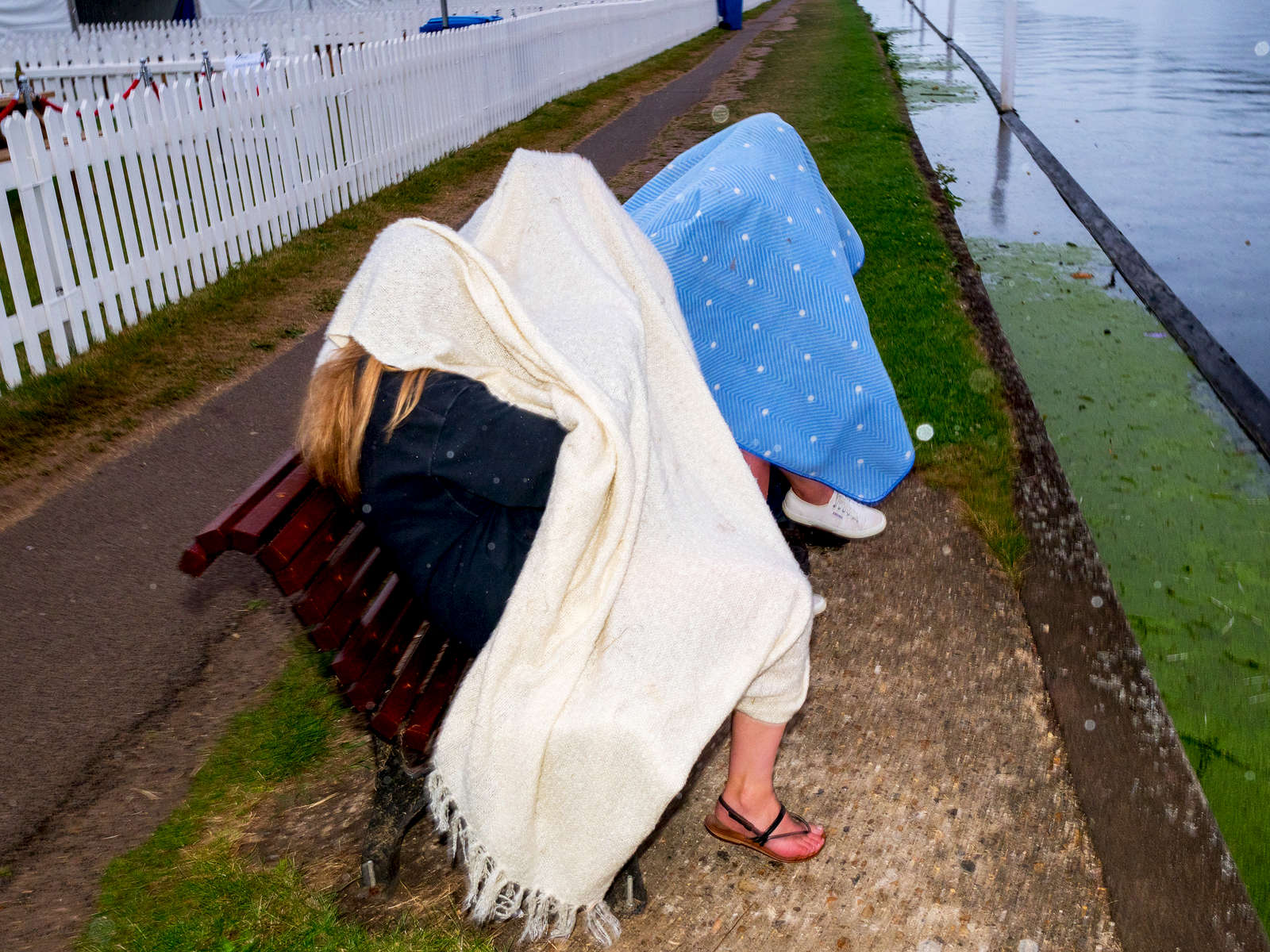 Friends try to keep dry from the rain under balnkets at Henley.Henley Royal Regatta is a rowing event held annually on the River Thames by the town of Henley-on-Thames, England. It was established on 26 March 1839.