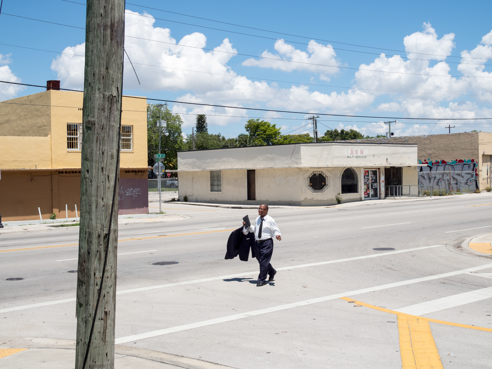 A man carrying his jacket after a Sunday church service in Little Haiti, a neighborhood of Miami, Florida, United States. It is home to many Haitian immigrant residents, as well as many residents from the rest of the Caribbean.Miami is a seaport city on the Atlantic Ocean in south Florida. Miami's metro area is the eighth-most populous and fourth-largest urban area in the U.S., with a population of around 5.5 million.Miami is a major center, and a leader in finance, commerce, culture, media, entertainment, the arts, and international trade. In 2008, Forbes magazine ranked Miami {quote}America's Cleanest City{quote}, for its year-round good air quality, vast green spaces, clean drinking water, clean streets, and city-wide recycling programs. According to a 2009 UBS study of 73 world cities, Miami was ranked as the richest city in the United States, and the world's fifth-richest city in terms of purchasing power. Miami is nicknamed the {quote}Capital of Latin America{quote}, is the second largest U.S. city with a Spanish-speaking majority, and the largest city with a Cuban-American plurality.©Peter Dench/Getty Images Reportage