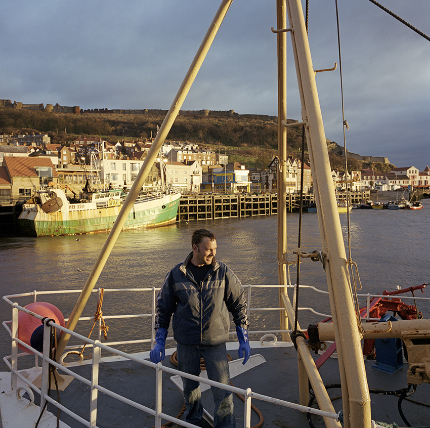 Tim onboard The Allegiance as it sets out from Scarborough to fish the North Sea.In 1999, Photojournalist Peter Dench spent five  days onboard The Allegiance, a 60 foot UK Scarborough-based trawler, fishing the North Sea, with a crew of five.  The future has since become extremely bleak for the English trawler men; huge areas of the North Sea have been declared \'off limits\' and fishing quotas have been slashed in an attempt to rescue dwindling North Sea stocks from the point of extinction.  These measures have jeopardised the jobs of those in the industry and put dependent towns, like Scarborough, on the brink of ruin.Dench returned to The Allegiance in 2005 to be reunited with the crew and to find out how the decline of the North Sea fishing industry has affected their lives.