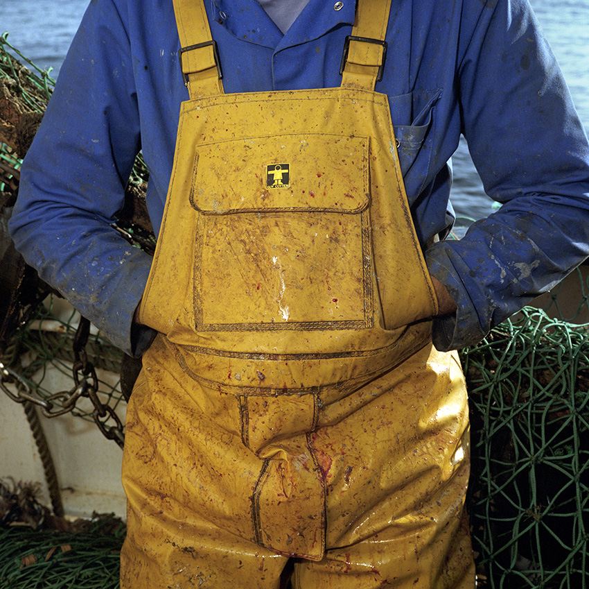 Waterproof oilskins are the essential uniform of any one working on a fishing trawler, but must be removed when inside the boat. The kit is supplied and paid for by each individual fisherman.In 1999, Photojournalist Peter Dench spent five days onboard The Allegiance, a 60 foot UK Scarborough-based trawler, fishing the North Sea, with a crew of five.  The future has since become extremely bleak for the English trawler men; huge areas of the North Sea have been declared \'off limits\' and fishing quotas have been slashed in an attempt to rescue dwindling North Sea stocks from the point of extinction.  These measures have jeopardised the jobs of those in the industry and put dependent towns, like Scarborough, on the brink of ruin.Dench returned to The Allegiance in 2005 to be reunited with the crew and to find out how the decline of the North Sea fishing industry has affected their lives.