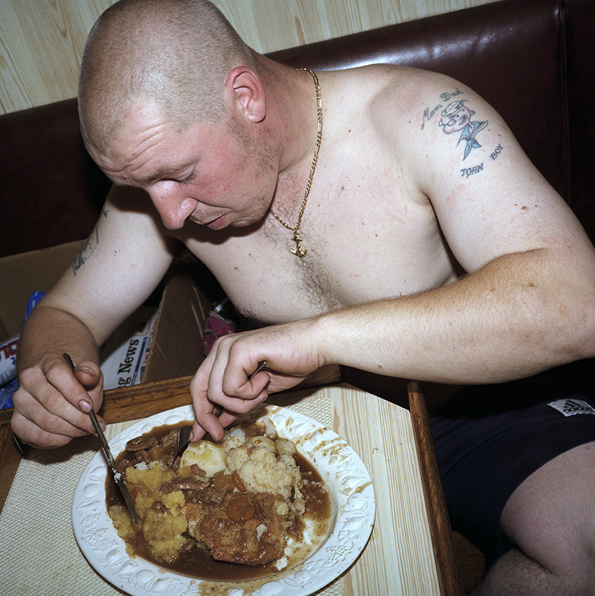 John Boy, a 22 year old geordie skinhead in 1999 tucking into a hearty meal of meat, potatoes and veg in the kitchen on board The Allegiance. In 1999, Photojournalist Peter Dench spent five  days onboard The Allegiance, a 60 foot UK Scarborough-based trawler, fishing the North Sea, with a crew of five.  The future has since become extremely bleak for the English trawler men; huge areas of the North Sea have been declared \'off limits\' and fishing quotas have been slashed in an attempt to rescue dwindling North Sea stocks from the point of extinction.  These measures have jeopardised the jobs of those in the industry and put dependent towns, like Scarborough, on the brink of ruin.Dench returned to The Allegiance in 2005 to be reunited with the crew and to find out how the decline of the North Sea fishing industry has affected their lives.