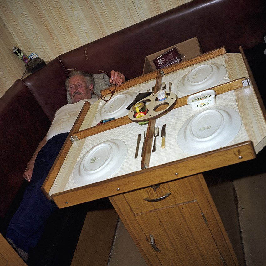 """George relaxes in the eating area where the table has raised edges to stop the plates from slipping off. In 1999, George, 65, was the longest serving member of The Allegiance and has worked the trawlers since the age of 15.  Also the ships cook, asked how he coped with cooking in a storm he replied: """"You just make the gravy thicker.\{quote}In 1999, Photojournalist Peter Dench spent five days onboard The Allegiance, a 60 foot UK Scarborough-based trawler, fishing the North Sea, with a crew of five.  The future has since become extremely bleak for the English trawler men; huge areas of the North Sea have been declared \'off limits\' and fishing quotas have been slashed in an attempt to rescue dwindling North Sea stocks from the point of extinction.  These measures have jeopardised the jobs of those in the industry and put dependent towns, like Scarborough, on the brink of ruin.Dench returned to The Allegiance in 2005 to be reunited with the crew and to find out how the decline of the North Sea fishing industry has affected their lives."""