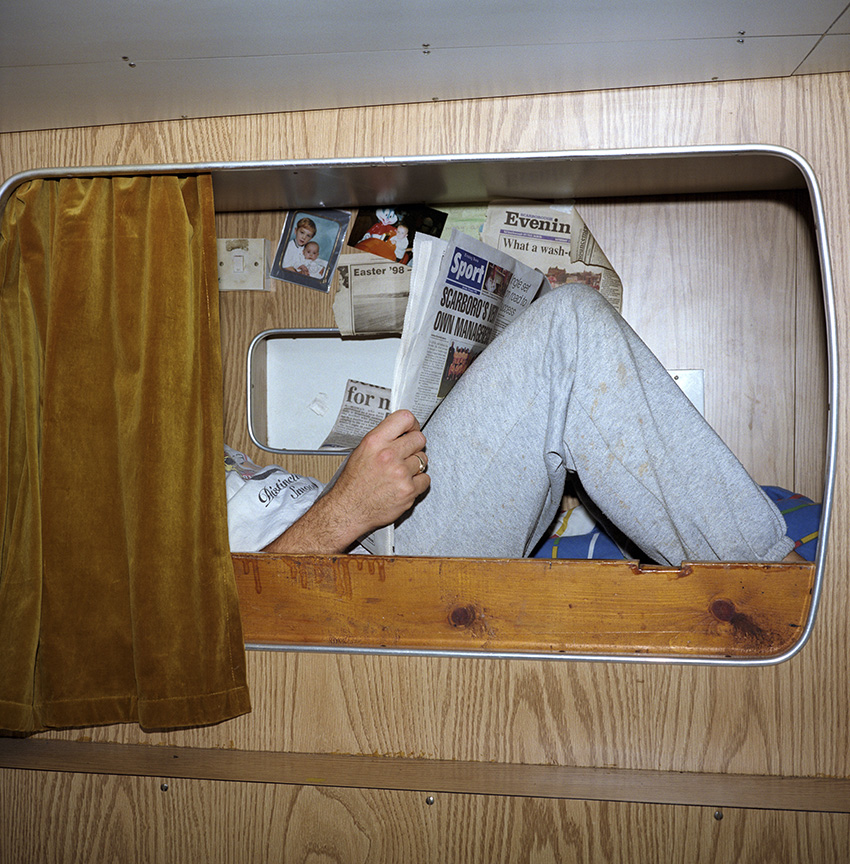 The room the crew sleeps in is a porthole less, fetid little cell - like a Scarborough caravan which has been wet and fishy for 20 years and used as a changing room for the local rugby team.  Fag stained plastic, wood grain-effect, laminated chipboard, vinyl and foam.  A tiny wet room below the water line and next to the ships engine. Tim tries to make his bunk more comforting with pictures of his family and reading the local news.In 1999, Photojournalist Peter Dench spent five days onboard The Allegiance, a 60 foot UK Scarborough-based trawler, fishing the North Sea, with a crew of five.  The future has since become extremely bleak for the English trawler men; huge areas of the North Sea have been declared \'off limits\' and fishing quotas have been slashed in an attempt to rescue dwindling North Sea stocks from the point of extinction.  These measures have jeopardised the jobs of those in the industry and put dependent towns, like Scarborough, on the brink of ruin.Dench returned to The Allegiance in 2005 to be reunited with the crew and to find out how the decline of the North Sea fishing industry has affected their lives.