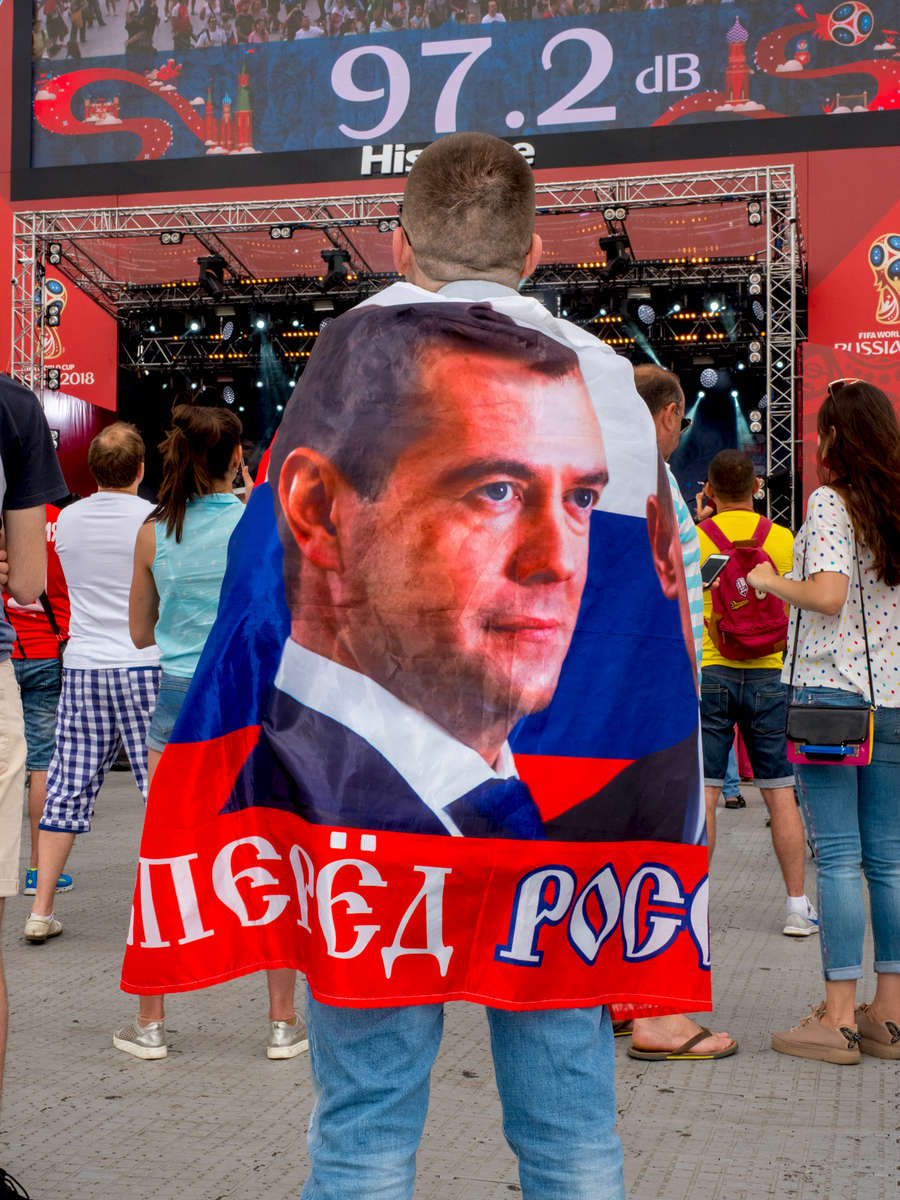 A fan with a flag featuring Dmitry Anatolyevich Medvedev, a Russian politician who has served as the Prime Minister of Russia since 2012. From 2008 to 2012, Medvedev served as the third President of Russia.The Moscow FIFA Fan Fest located at Vorobyovy Gory (Sparrow Hills) with a venue Capacity of 25,000. The site provides a spectacular view down the hill, directly towards Luzhniki Stadium and Moscow City. The 21st FIFA World Cup football tournament took place in Russia in 2018. It was the first World Cup to be held in Eastern Europe and the eleventh time that it has been held in Europe. For the first time the tournament took place on two continents – Europe and Asia. All but two of the stadium venues were in European Russia.