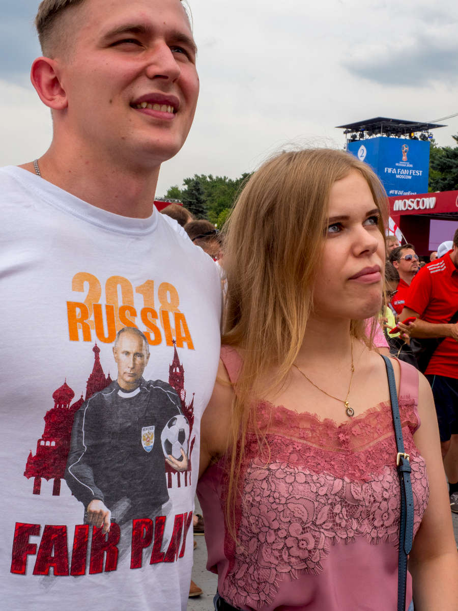 A Russian fan at the FIFA Fan Fest wearing aPutin inspired T-Shirt. The Moscow FIFA Fan Fest located at Vorobyovy Gory (Sparrow Hills) with a venue Capacity of 25,000. The site provides a spectacular view down the hill, directly towards Luzhniki Stadium and Moscow City. Vladimir Vladimirovich Putin is a Russian statesman and former intelligence officer serving as President of Russia since 2012, previously holding the position from 2000 until 2008. The 21st FIFA World Cup football tournament took place in Russia in 2018. It was the first World Cup to be held in Eastern Europe and the eleventh time that it has been held in Europe. For the first time the tournament took place on two continents – Europe and Asia. All but two of the stadium venues were in European Russia.