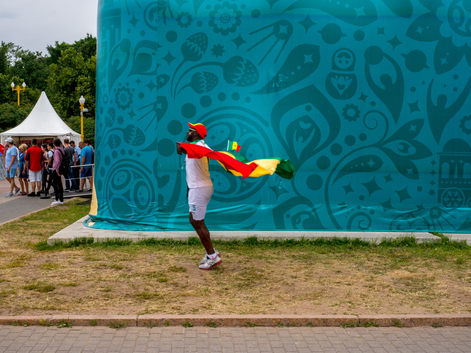 A Senegal football fan arrives at the Moscow FIFA Fan Fest located at Vorobyovy Gory (Sparrow Hills) with a venue Capacity of 25,000. The site provides a spectacular view down the hill, directly towards Luzhniki Stadium and Moscow City. The 21st FIFA World Cup football tournament took place in Russia in 2018. It was the first World Cup to be held in Eastern Europe and the eleventh time that it has been held in Europe. For the first time the tournament took place on two continents – Europe and Asia. All but two of the stadium venues were in European Russia.