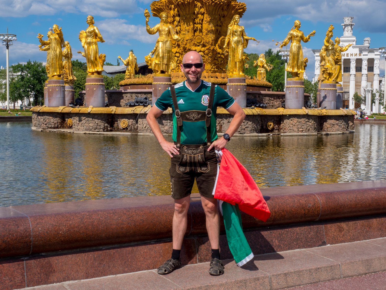 A Mexican football fan wearing traditional German Lederhosen poses for a photograph  by the Friendship of Nations fountain. The 21st FIFA World Cup football tournament took place in Russia in 2018. It was the first World Cup to be held in Eastern Europe and the eleventh time that it has been held in Europe. For the first time the tournament took place on two continents – Europe and Asia. All but two of the stadium venues were in European Russia.
