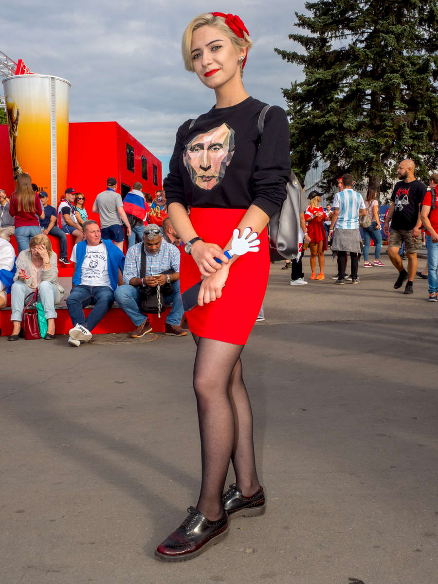 A Russian football fan with a T-Shirt featuring Vladimir Putin. Vladimir Vladimirovich Putin is a Russian statesman and former intelligence officer serving as President of Russia since 2012, previously holding the position from 2000 until 2008. The Moscow FIFA Fan Fest located at Vorobyovy Gory (Sparrow Hills) with a venue Capacity of 25,000. The site provides a spectacular view down the hill, directly towards Luzhniki Stadium and Moscow City. The 21st FIFA World Cup football tournament took place in Russia in 2018. It was the first World Cup to be held in Eastern Europe and the eleventh time that it has been held in Europe. For the first time the tournament took place on two continents – Europe and Asia. All but two of the stadium venues were in European Russia.